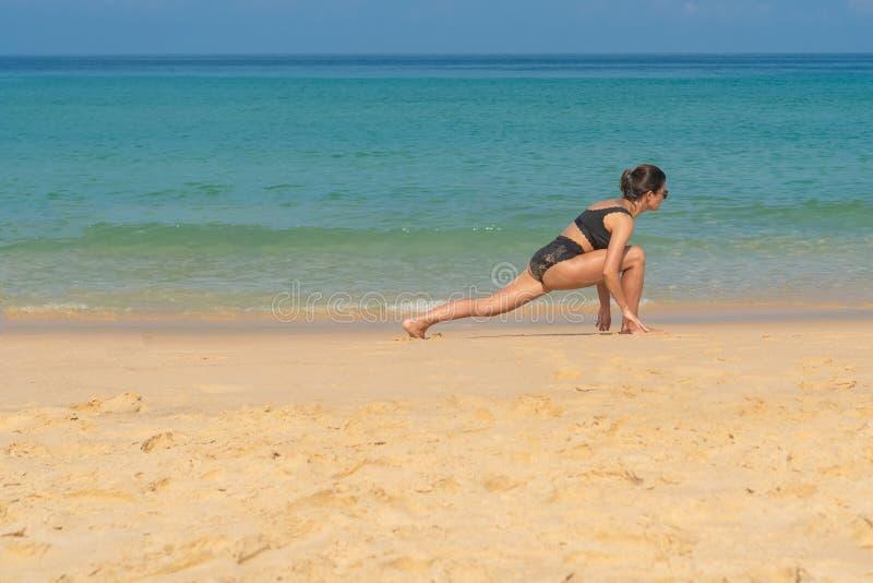 Phuket, Tailandia - 30 de marzo de 2019: Muchacha delgada en un bañador negro que hace la yoga Pilates en la playa fotos de archivo