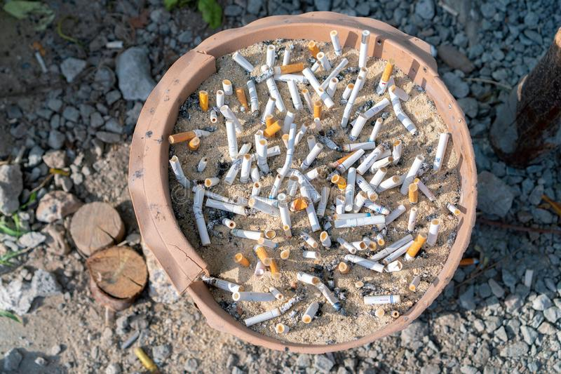 Phuket, Tailandia - 27 marzo 2019: La sigaretta si intromette il portacenere con la sabbia a punto di formazione del fumo fotografie stock
