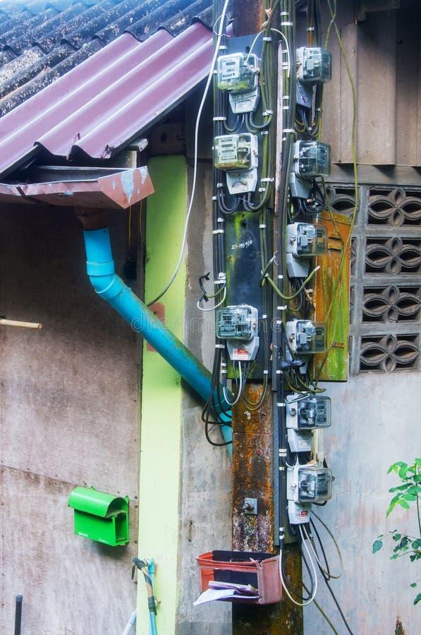 PHUKET, TAILANDIA - 23 MARZO 2017: Molti metri di elettricità su un palo arrugginito immagini stock libere da diritti