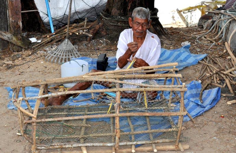 Phuket, Tailandia: Rete di presa di riparazione del pescatore fotografie stock