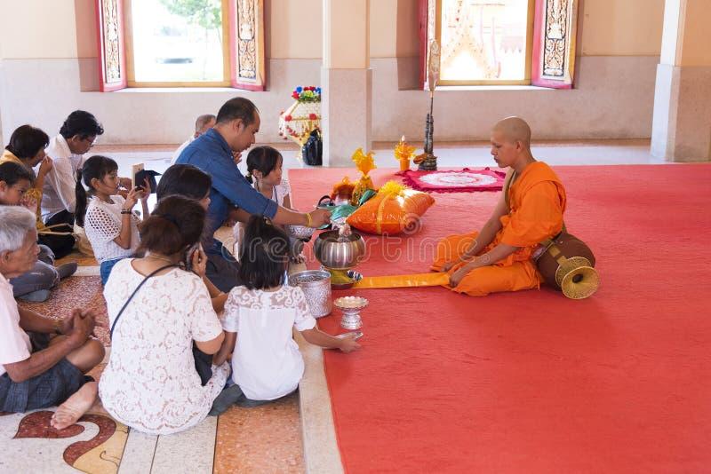Phuket, Tailandia, 04/19/2019 - singolo monaco buddista che prega con una famiglia al tempio di Chalong fotografia stock libera da diritti