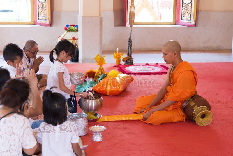 Phuket, Tailandia, 04/19/2019 - singolo monaco buddista che prega con una famiglia al tempio di Chalong immagine stock