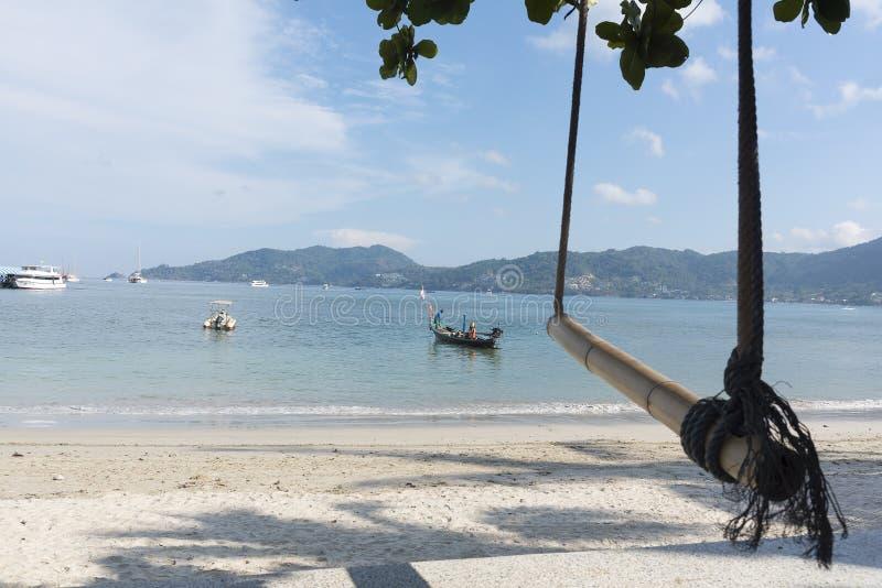 Phuket, Tailandia, spiaggia di Patong, 04/19/2019: esaminare il mare verso un continente con il peschereccio in priorità alta immagini stock