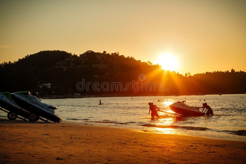 Phuket, Thaïlande - 2 février 2019 : Hommes au ski de jet de traction de coucher du soleil hors de l'eau sur une plage sablonneus image libre de droits