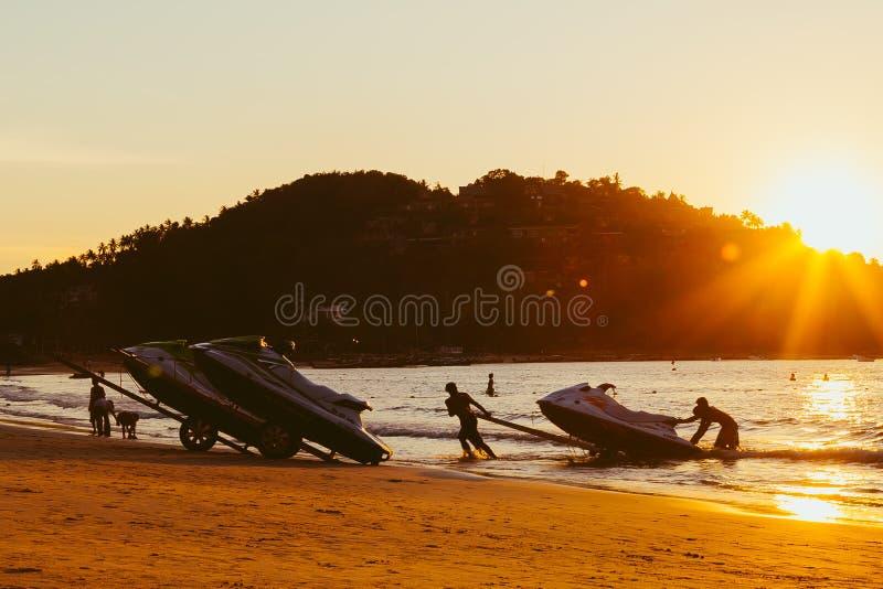 Phuket, Thaïlande - 2 février 2019 : Hommes au ski de jet de traction de coucher du soleil hors de l'eau sur une plage sablonneus photos libres de droits