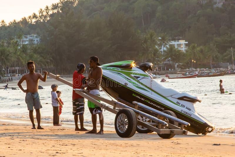 Phuket, Thaïlande - 2 février 2019 : Hommes au ski de jet de traction de coucher du soleil hors de l'eau sur une plage sablonneus images stock