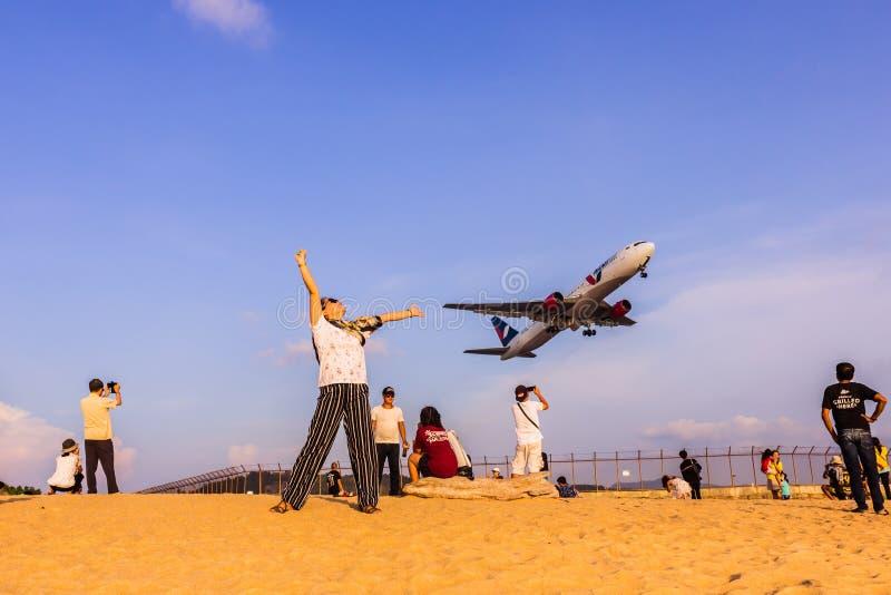 Phuket, Tha?lande - 14 avril 2019 : Les touristes ont plaisir ? prendre une photo avec l'avion volant au-dessus de eux comme fond photographie stock