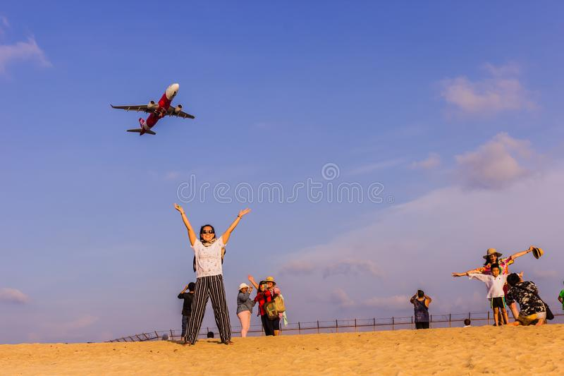 Phuket, Thailand - April 14, 2019: Tourists enjoy taking a picture with the airplane flying over them as the background, at the stock photo