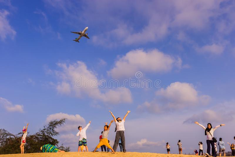 Phuket, Thailand - April 14, 2019: Tourists enjoy taking a picture with the airplane flying over them as the background, at the. Mai Khao Beach, the edge of stock image