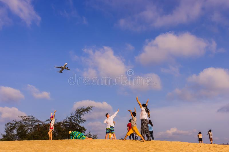 Phuket, Thailand - April 14, 2019: Tourists enjoy taking a picture with the airplane flying over them as the background, at the. Mai Khao Beach, the edge of stock photography