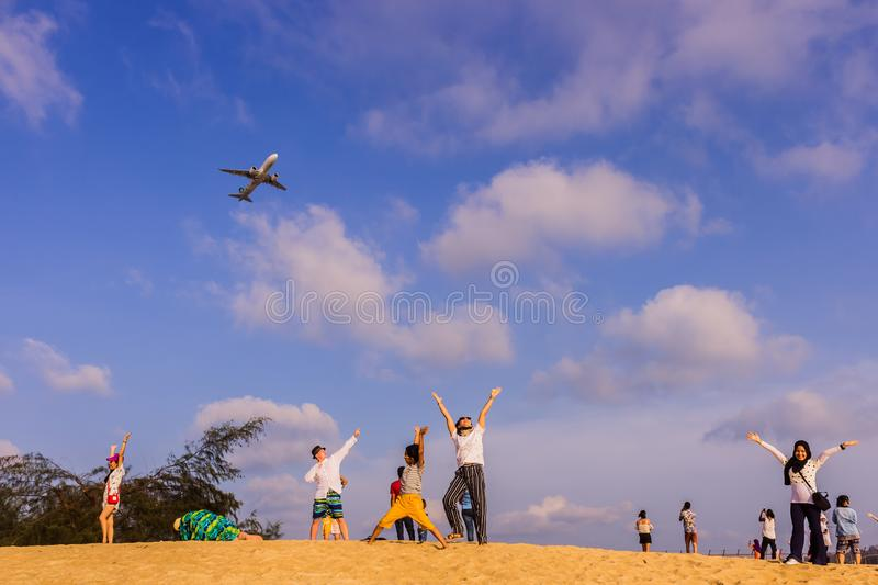 Phuket, Thailand - April 14, 2019: Tourists enjoy taking a picture with the airplane flying over them as the background, at the. Mai Khao Beach, the edge of stock photo