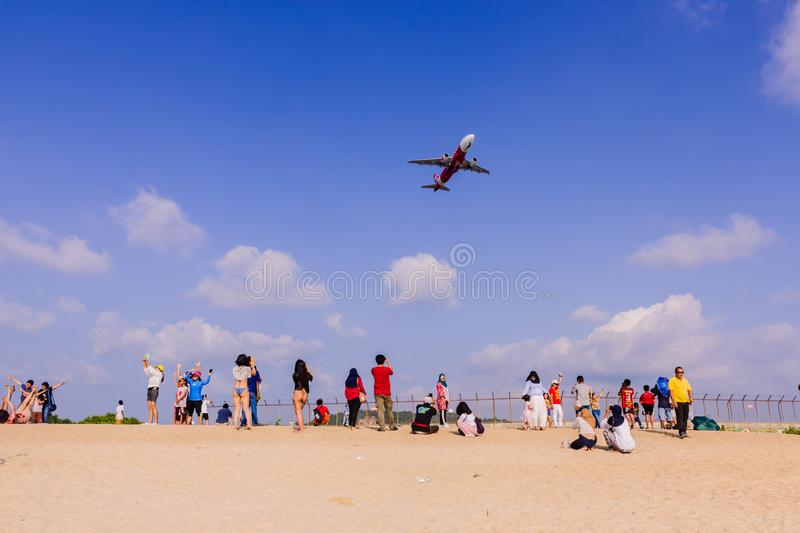 Phuket, Thailand - April 14, 2019: Tourists enjoy taking a picture with the airplane flying over them as the background, at the royalty free stock photography