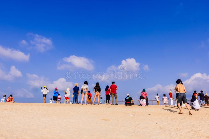Phuket, Thailand - April 14, 2019: Tourists enjoy taking a picture with the airplane flying over them as the background, at the stock image