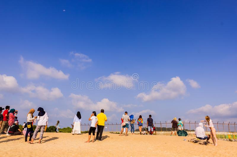 Phuket, Thailand - April 14, 2019: Tourists enjoy taking a picture with the airplane flying over them as the background, at the. Mai Khao Beach, the edge of royalty free stock photos
