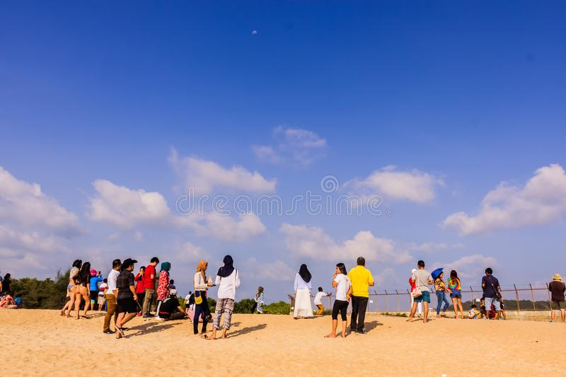 Phuket, Thailand - April 14, 2019: Tourists enjoy taking a picture with the airplane flying over them as the background, at the. Mai Khao Beach, the edge of royalty free stock image