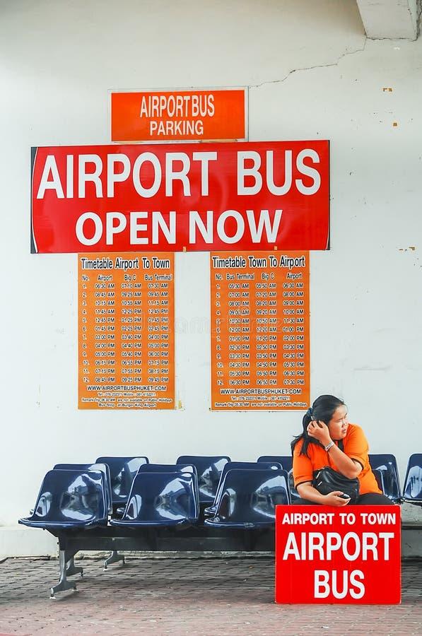 Phuket, Thailand - 2009: Een dame die op luchthavenbus bij de Internationale Luchthaven van Phuket wachten stock afbeeldingen