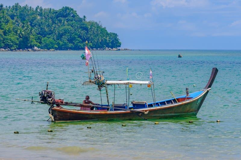 Phuket thailand 08/05/2018 - Een visserszitting in zijn lange staartboot stock afbeeldingen
