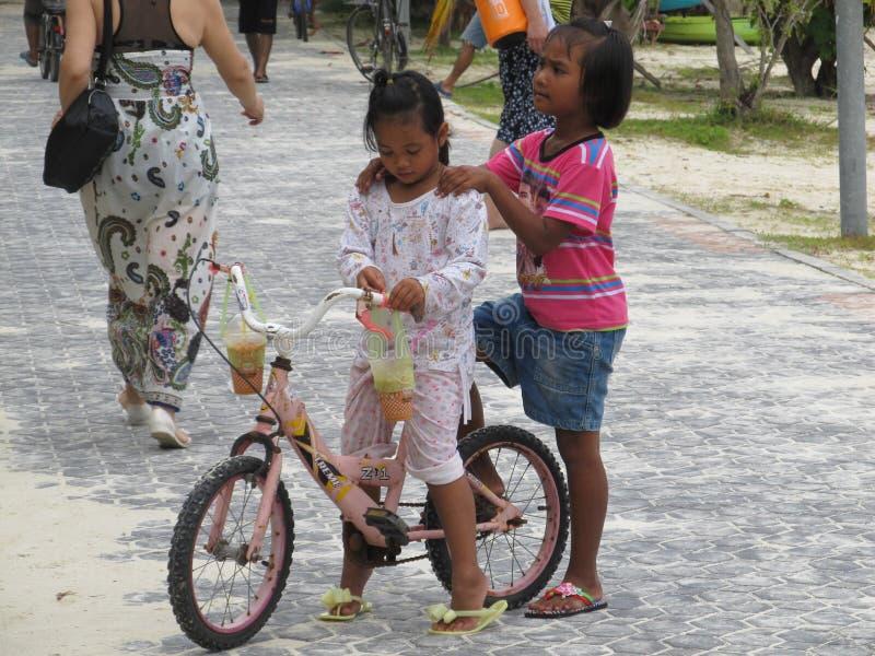 Phuket, Phuket Thailand - 10 15 2012: het donker-gevilde Aziatische meisje houdt haar vriend door de schouders die met haar fiets royalty-vrije stock foto's