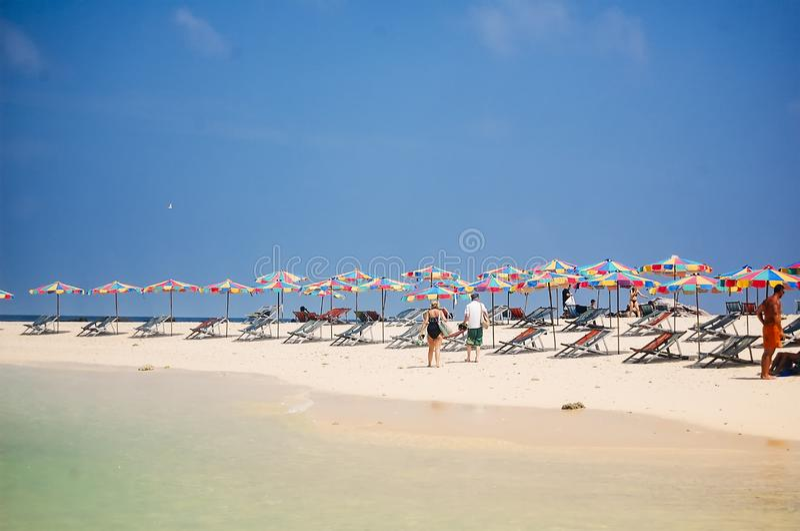 Phuket, Thailand - 2009: Ligstoelen en kleurrijke paraplu'slijn het strand royalty-vrije stock foto