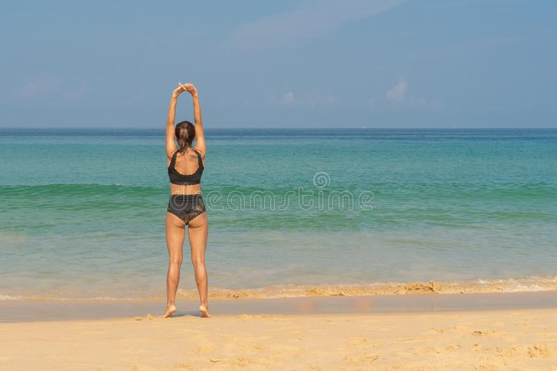 Phuket, Thailand - March 30, 2019: Slender girl in a black bathing suit with a tattoo on his shoulder doing yoga royalty free stock images