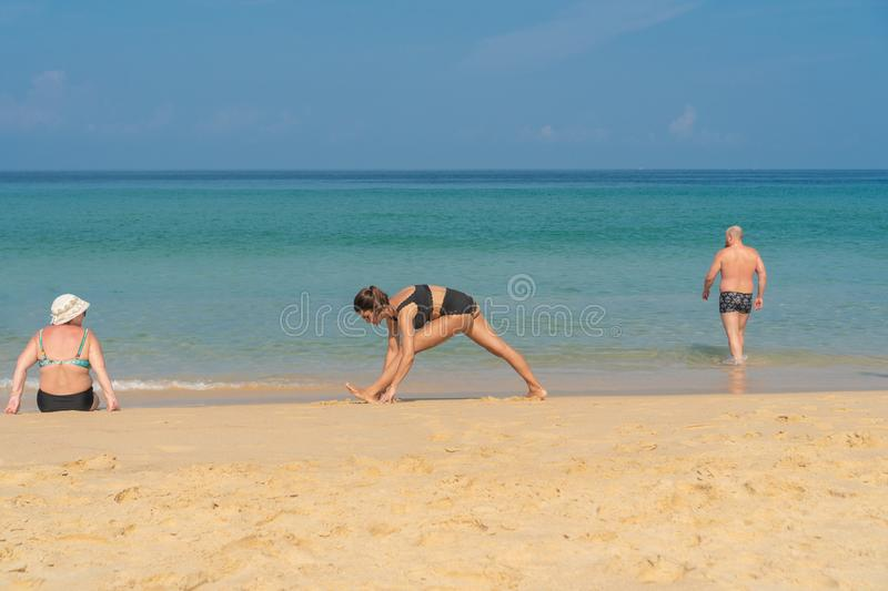 Phuket, Thailand - March 30, 2019: Slender girl in a black bathing suit with a tattoo on his shoulder doing yoga Pilates on the stock images