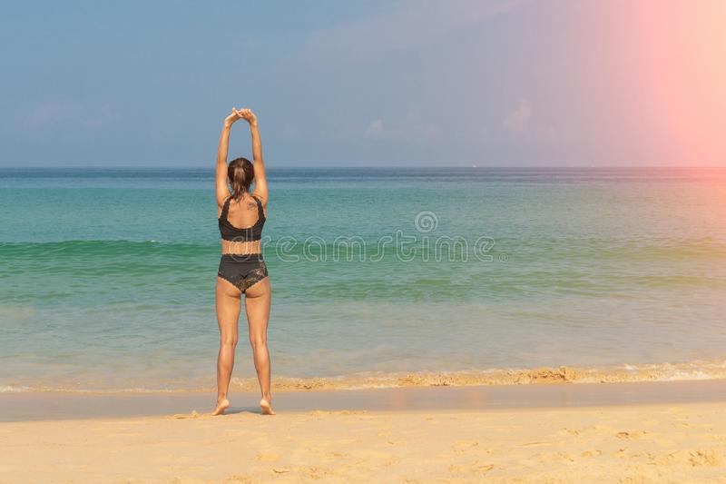 Phuket, Thailand - March 30, 2019: Slender girl in a black bathing suit with a tattoo on his shoulder doing yoga Pilates on the stock photos