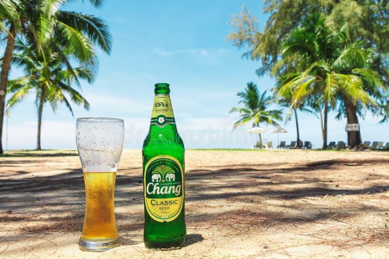 Phuket Thailand - marknad 6, 2018: Flaska och exponeringsglas av kallt Chang öl på sanden på bakgrunden av gröna palmträd royaltyfri fotografi