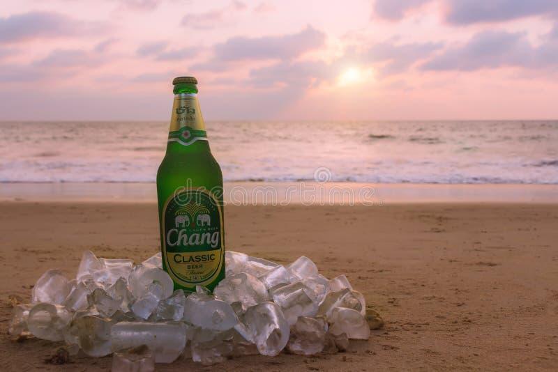 Phuket Thailand - marknad 11, 2019: misted flaska av kallt Chang ?l p? sanden p? bakgrunden av seascape, solnedg?nghimmel och hav arkivbild