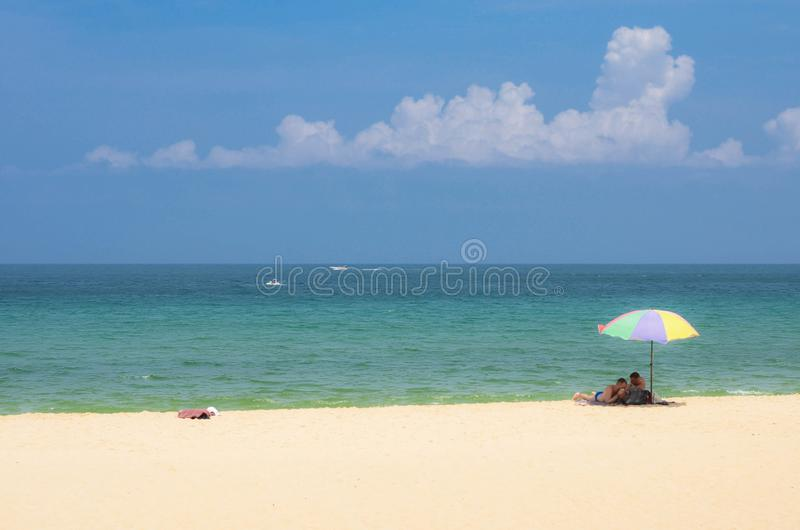 Happy couple men under colourful umbrella are resting on the beautiful tropical beach at Phuket stock image