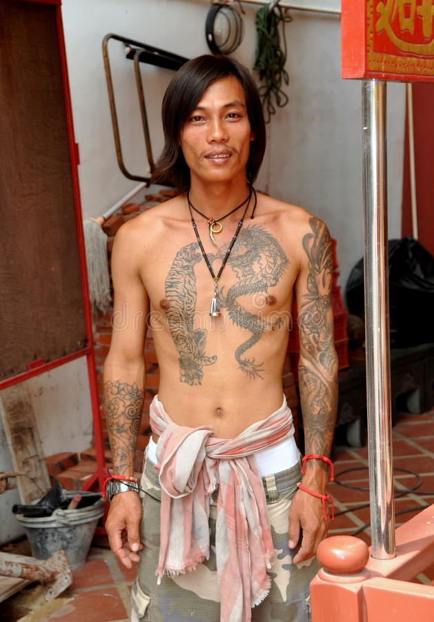 Phuket, Thailand: Tattooed Thai Man. Young Thai construction worker in Phuket City on Phuket Island, Thailand shows off his arm and chest tattoos which include a stock photos