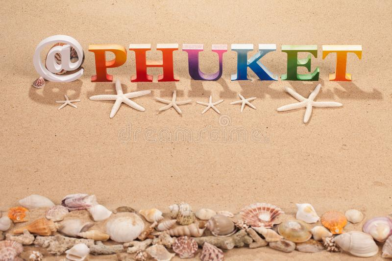 @Phuket written in colorful wood letters at the beach. @Phuket written in colorful wood letters with sea shell at the beach with copy space royalty free stock photography