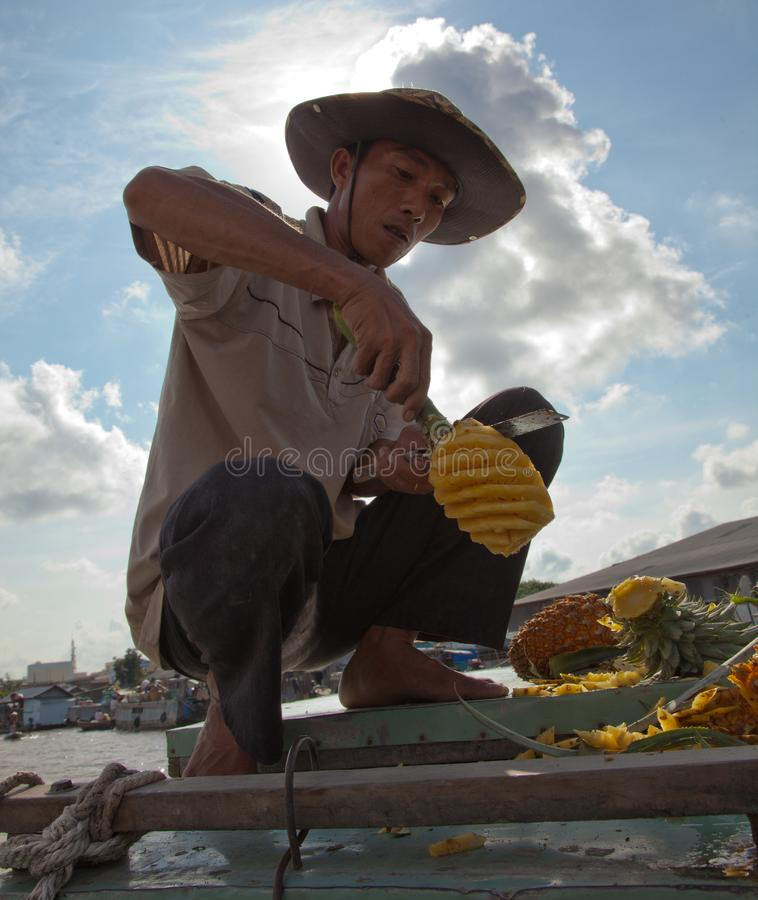 Phung Hiep, Vietnam / Oct 17, 2011: Man expertly slices a pinneaple for eating. At the floating market stock photography