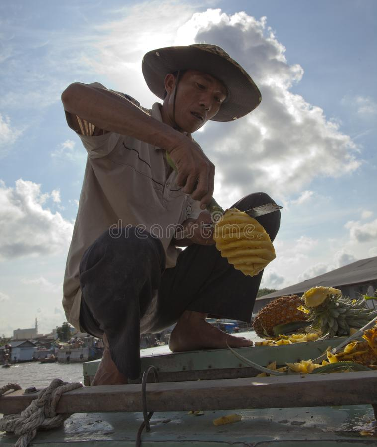 Phung Hiep, Vietnam - Oct 17, 2011: Man expertly slices a pinneaple for eating. At the floating market royalty free stock images