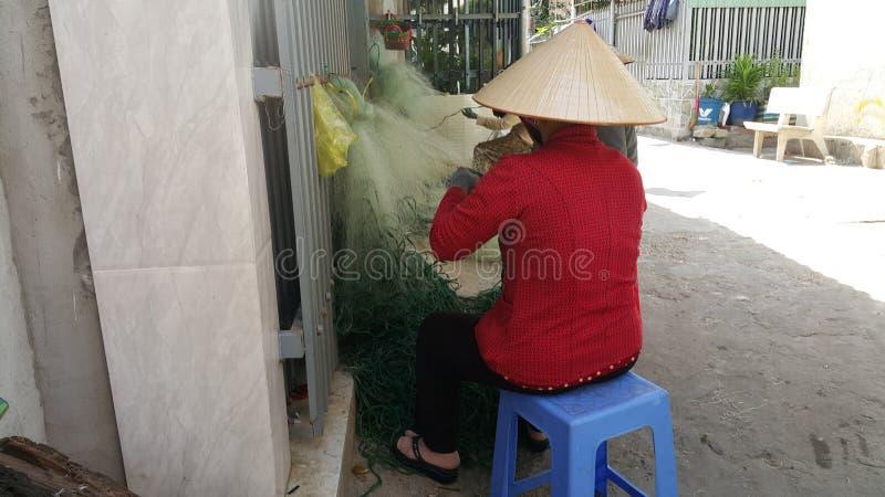 Phuoc Hiep, Vietnam - 04 29 2019: Las mujeres están haciendo punto redes de pesca imagen de archivo libre de regalías