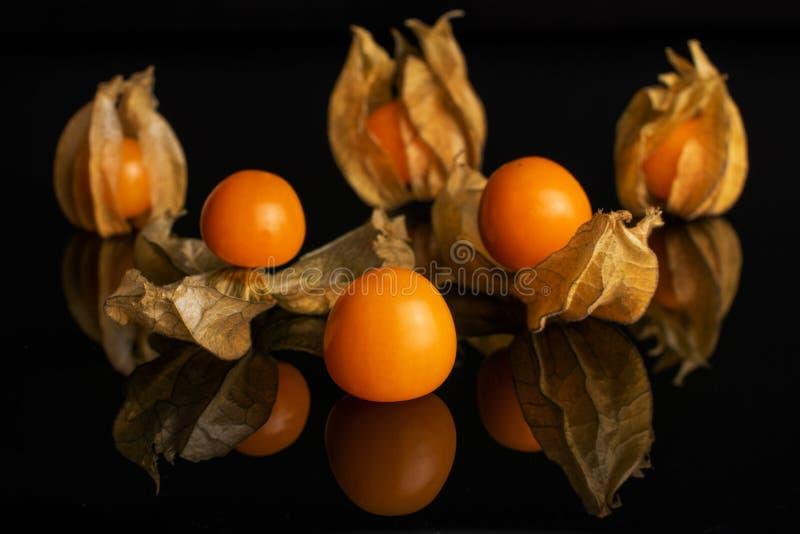 Physalis arancio fresco isolato su vetro nero immagine stock