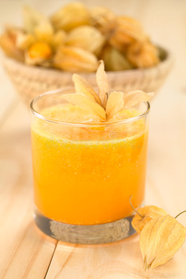 Physalis Juice. Freshly prepared juice made of physalis (lat. Physalis peruviana) served in glass with physalis fruits on the side and a basket full of physalis stock photos