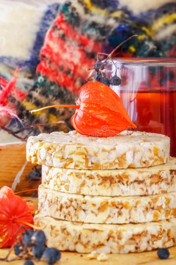 Physalis on puffed wheat cake, wild forest berries and fruit tea with lemon on a wooden table. Dietary food. royalty free stock photo