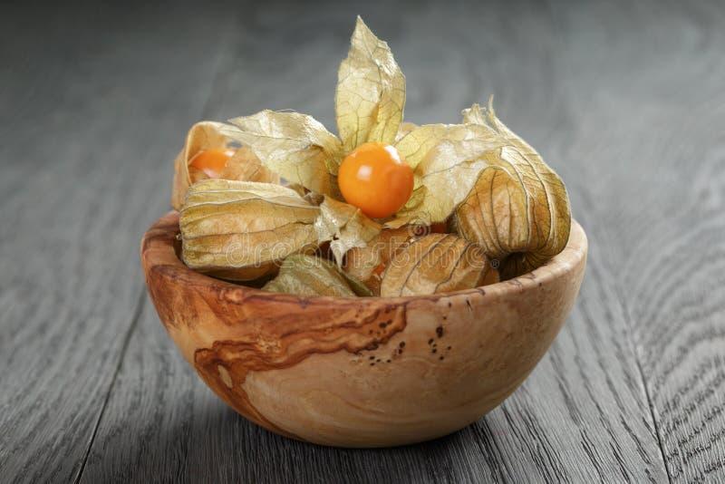 Physalisfruit in olijfkom op eiken houten lijst royalty-vrije stock afbeelding
