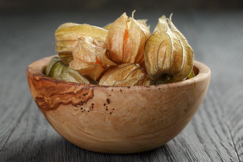 Physalisfruit in olijfkom op eiken houten lijst stock fotografie