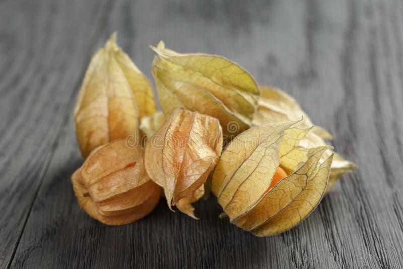 Physalisfruit op eiken houten lijst stock afbeeldingen