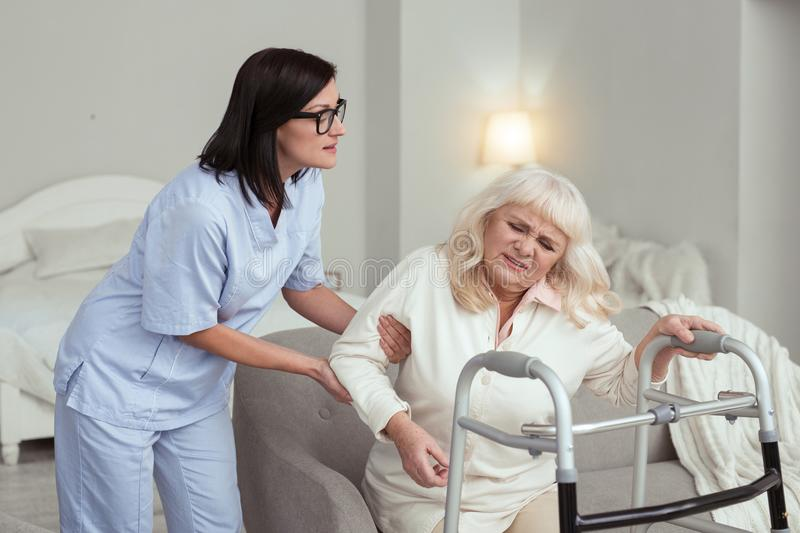 Attentive nurse aiding elder woman. Physical activity. Professional nurse helping elder women who experiencing pain royalty free stock image