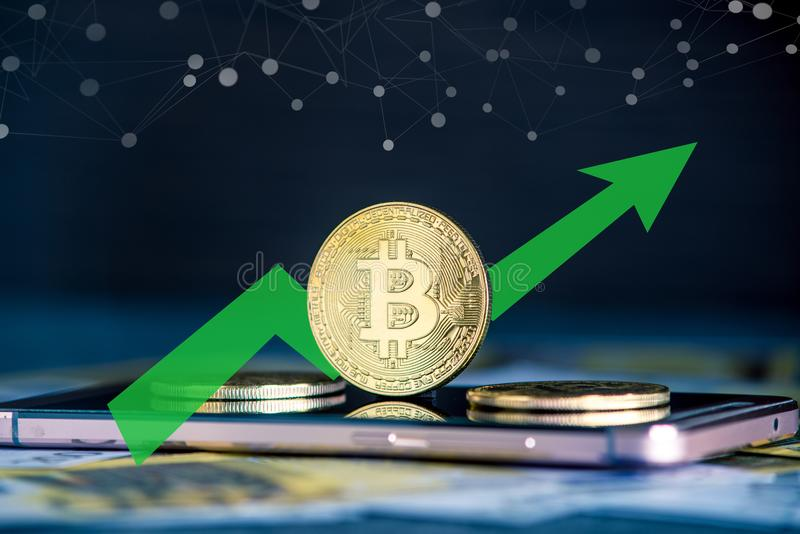 Bitcoin coin on the phone screen on the background of the Euro banknotes. Green arrow of the price growth chart. Physical bitcoin coin on the phone screen on the royalty free stock images