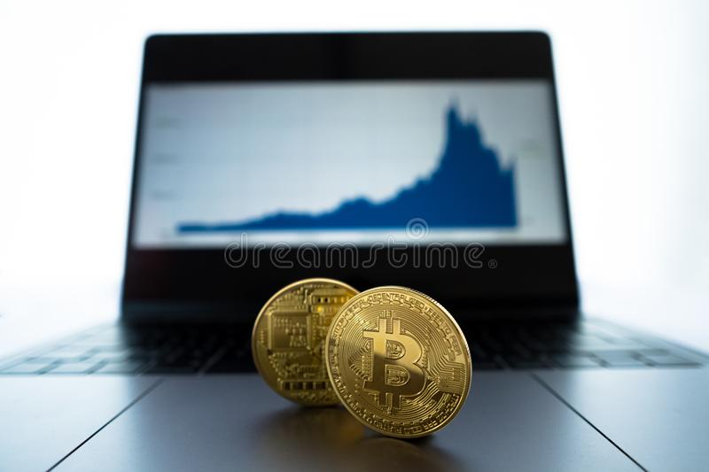Physical Bitcoin in front of laptop showing chart of recent performance. Physical gold conceptual Bitcoin in focus with shallow depth of field in front of laptop stock images