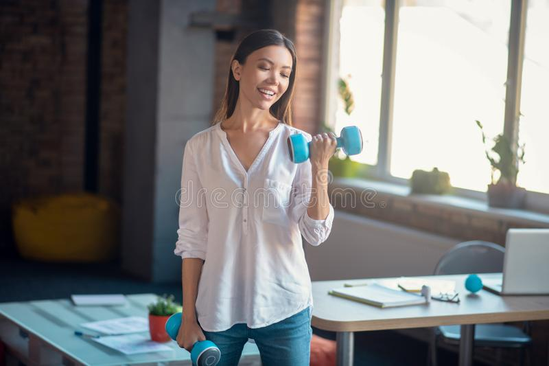Pretty slim woman having a workout in the office stock photos