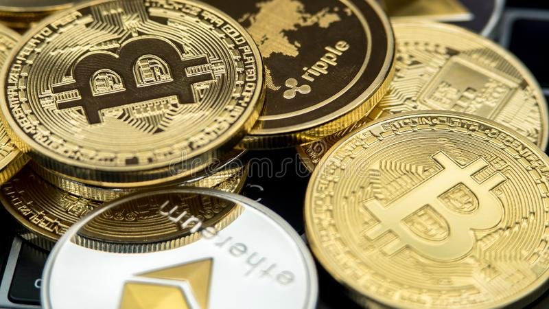 Physical metal currency on notebook computer keyboard. New Cryptocurrency stock photo