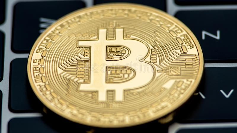 Physical metal golden Bitcoin currency on notebook computer keyboard. BTC royalty free stock photo