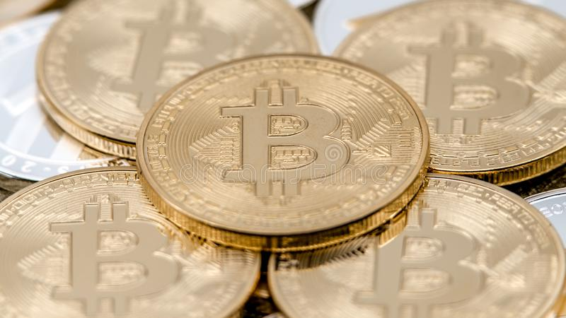 Physical metal golden Bitcoin currency rotating over others coins. BTC stock image