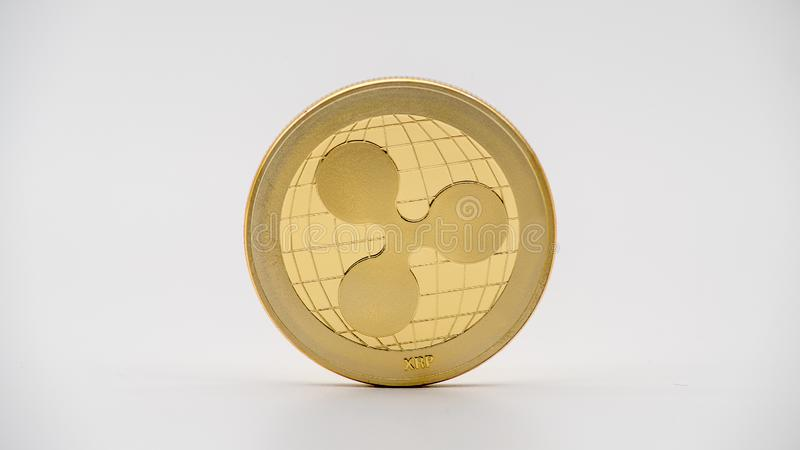 Physical metal golden Ripplecoin currency on white background. XRP coin stock image