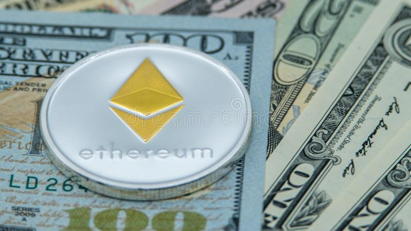 Physical metal silver Ethereum currency over diferents dollars bills. ETH stock photo