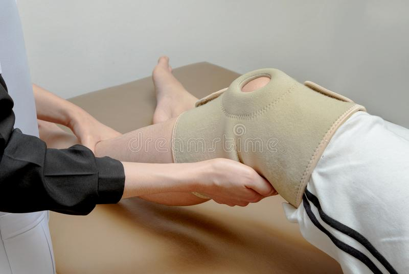 Physical therapist applying knee support to patient knee,rehabilitation royalty free stock photo